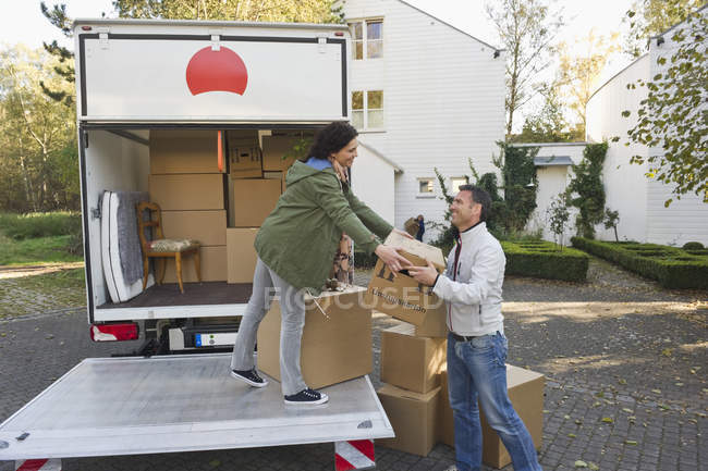 Couple loading boxes into truck, moving house concept — Stock Photo