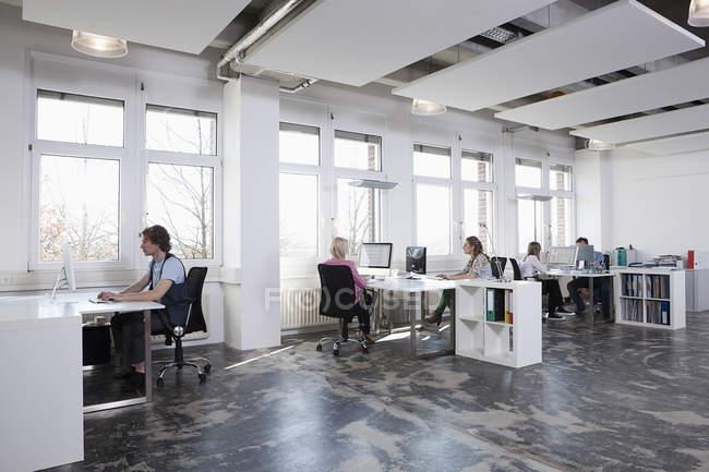 Hombres y mujeres que trabajan en equipo en oficina - foto de stock