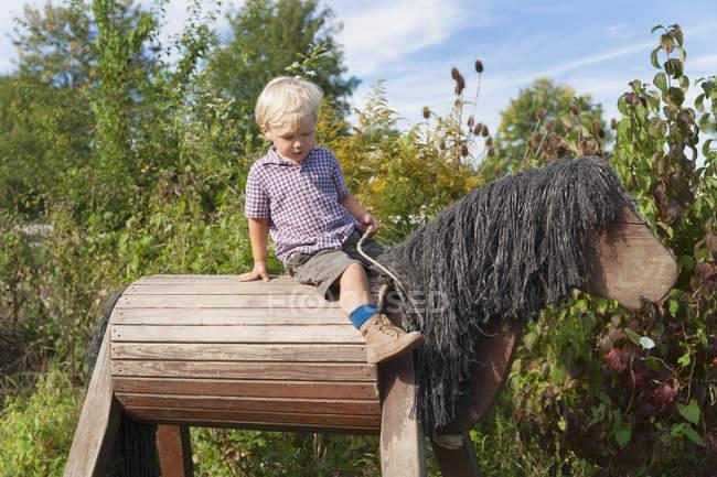 Jovem caucasiano menino sentado no cavalo de madeira no jardim — Fotografia de Stock