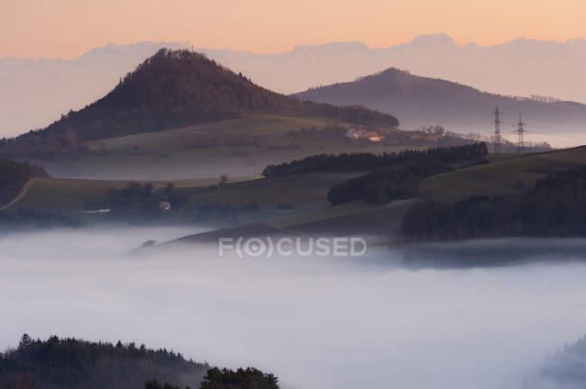 Montañas brumosas en el crepúsculo - foto de stock