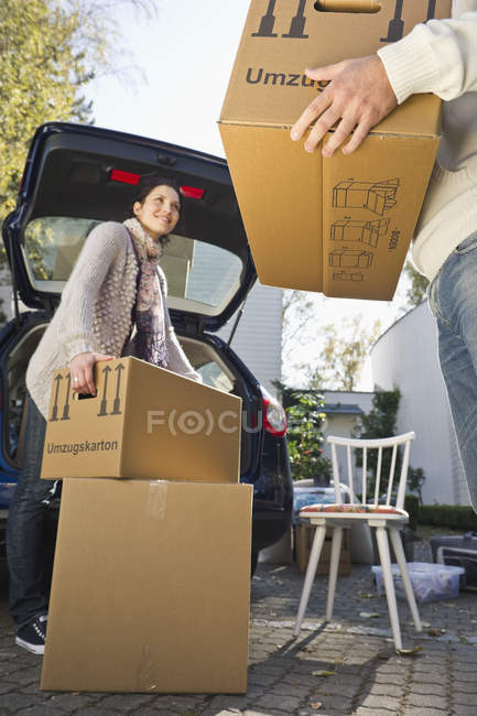 Couple loading boxes into car, moving house concept — Stock Photo