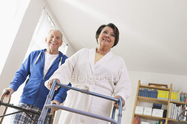 Senior man and woman with walking frame — Stock Photo
