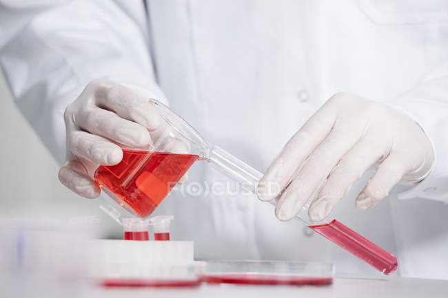 Scientist pouring red liquid — Stock Photo