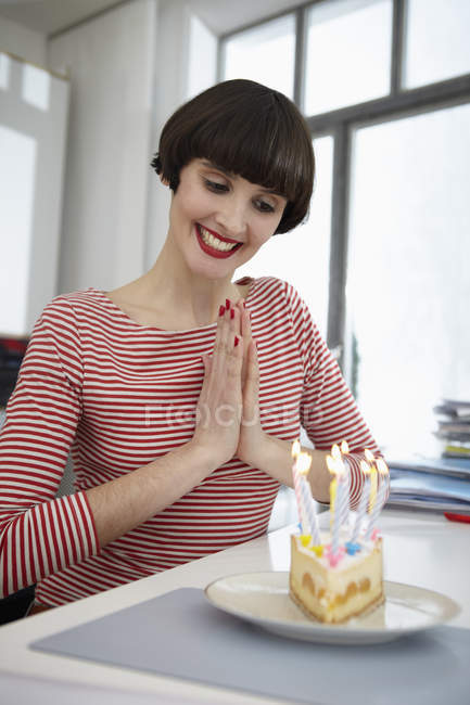 Young woman with birthday cake in apartment — Stock Photo