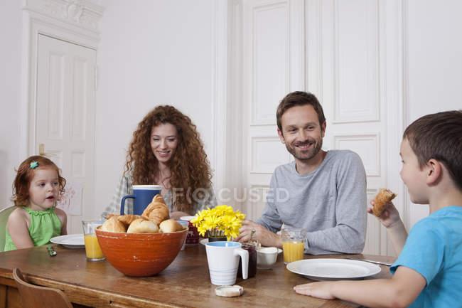 Счастливая семья завтракает на кухне дома — стоковое фото