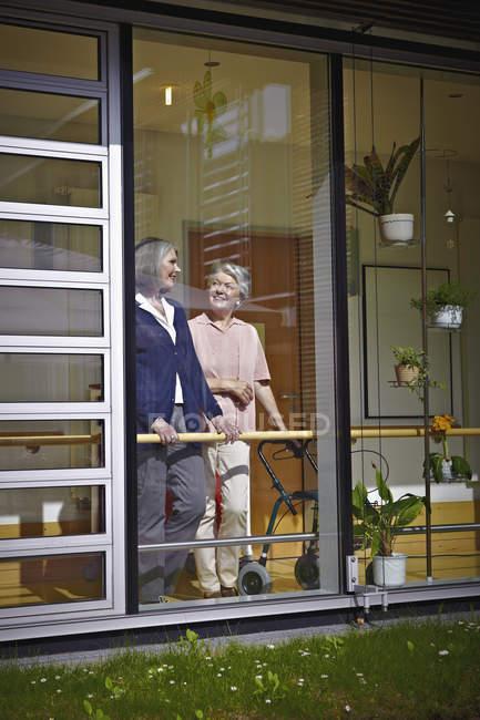 Smiling senior women in nursing home behind glass pane — Stock Photo