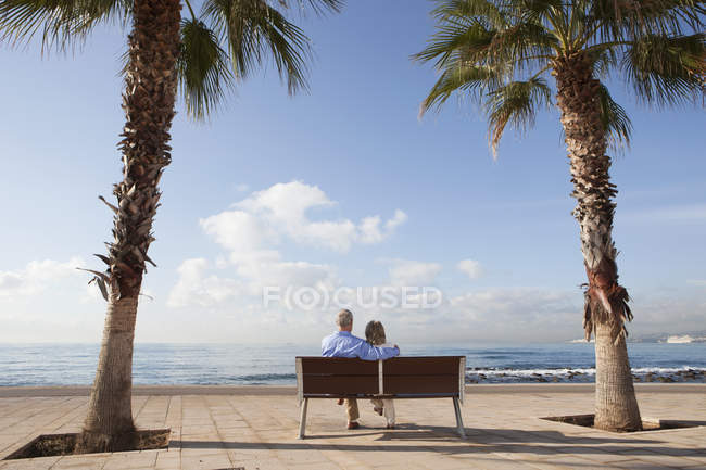 Spain, Mallorca, Senior couple sitting on bench at sea shore — Stock Photo
