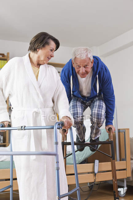 Старший мужчина и женщина с ходячей рамкой во время прыжка мужчины — стоковое фото