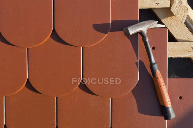 Кіготь молот на коричневий черепичної покрівлі під час будівництва — стокове фото