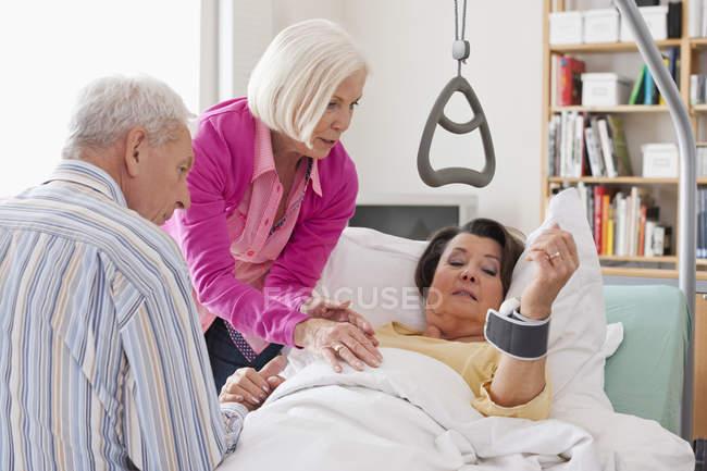 Senior mulher deitada na cama, homem e mulher sentados ao lado — Fotografia de Stock