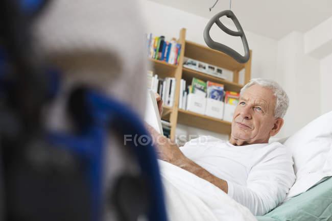 Homme âgé allongé sur un lit médical — Photo de stock