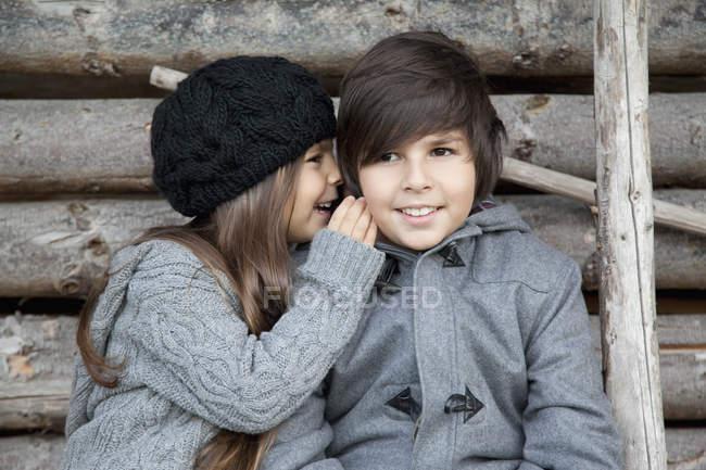 Junge und Mädchen flüstern einander zu — Stockfoto