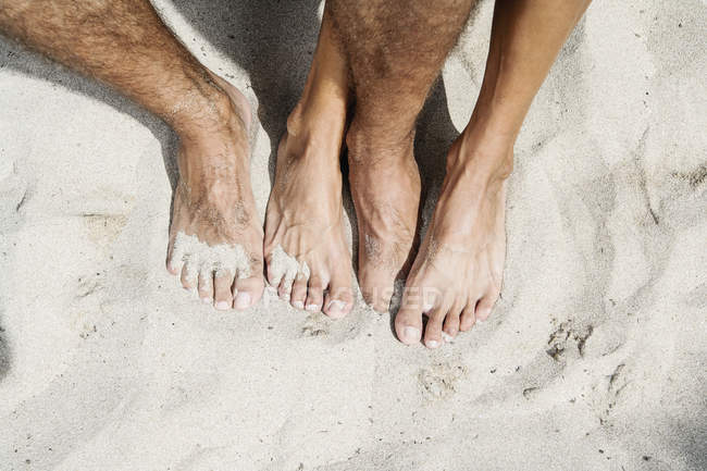 Mid adult couple legs on sandy beach, top view — Stock Photo