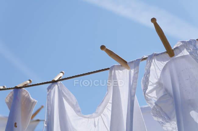 Сушіння білизни на миття лінії з синього неба на тлі — стокове фото