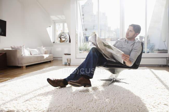 Uomo che legge il giornale nel salotto — Foto stock