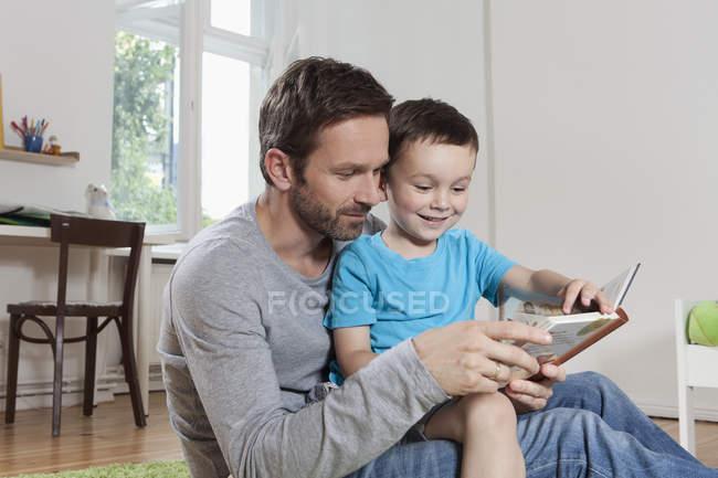 Батько і син читання книги — стокове фото