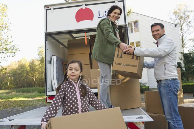 Famille avec une boîte en carton pour déménagement — Photo de stock