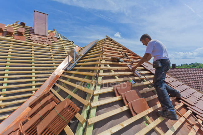 Средний взрослый мужчина измеряет плитку на крыше — стоковое фото