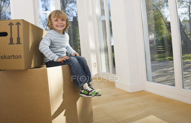 Boy sitting on cardboard box, moving house concept — Stock Photo