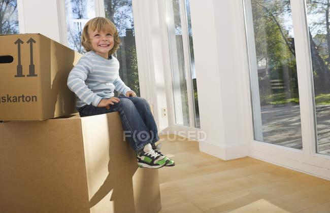 Niño sentado en la caja de cartón, móvil concepto casa - foto de stock