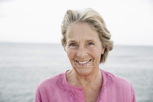 Senior woman smiling at Atlantic ocean — Stock Photo