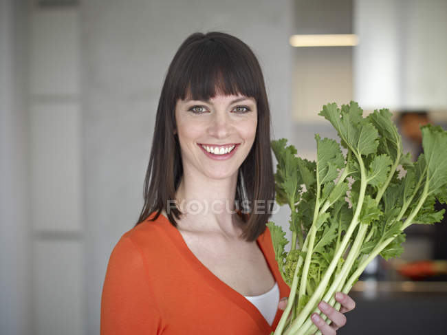 Mujer adulta media holding vegetal, Sonriente, retrato - foto de stock