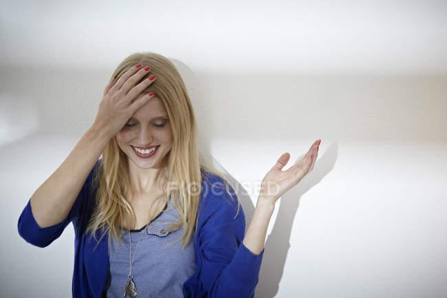 Молодая женщина улыбается на белой стене — стоковое фото
