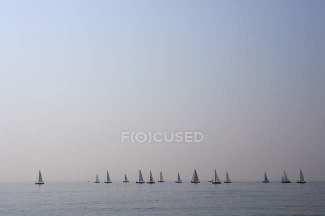 Italy, Province of Venice, Caorle, Sailboats in Adriatic Sea at dusk — Stock Photo