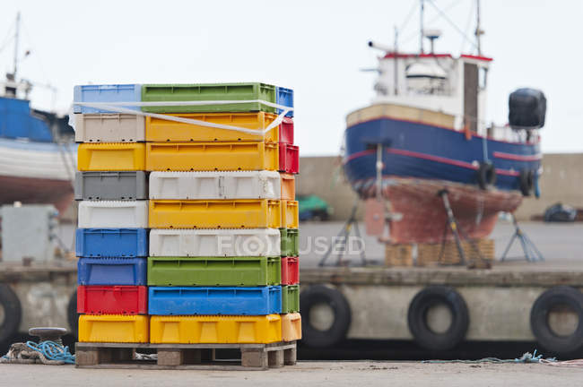 Sweden, Simrishamn, Stack of boxes for seafood on harbour — Stock Photo