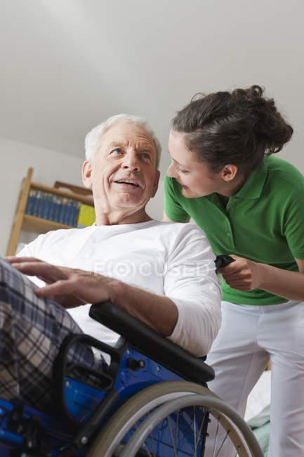 Homem em cadeira de rodas, conversando com mulher — Fotografia de Stock