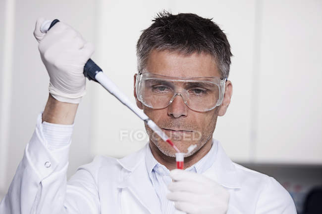 Scientist pouring red liquid with pipette — Stock Photo