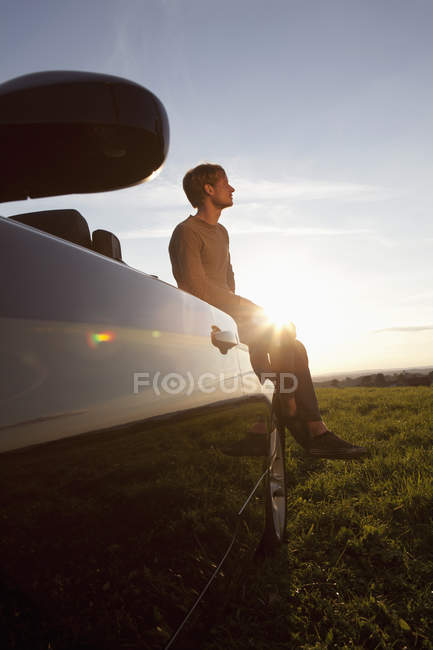 Man sitting on car at sunset — Stock Photo