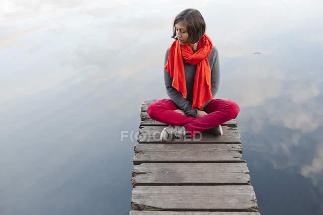 Mulher adulta média sentada no cais no lago th — Fotografia de Stock