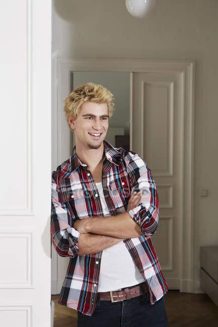Jovem de pé ao lado da porta, sorrindo — Fotografia de Stock