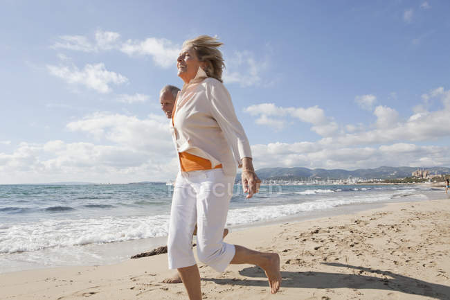 Senior couple running along beach, smiling — Stock Photo