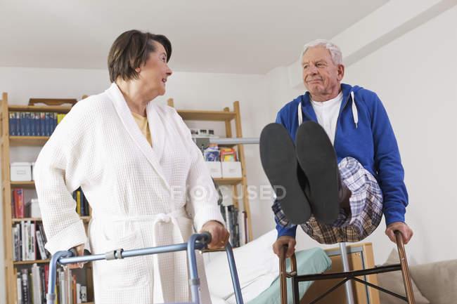 Старшая женщина стоит и мужчина играет с ходячей рамкой — стоковое фото