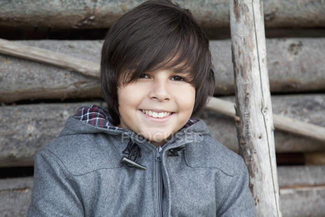 Портрет улыбающегося мальчика, сидящего в деревянной хижине — стоковое фото