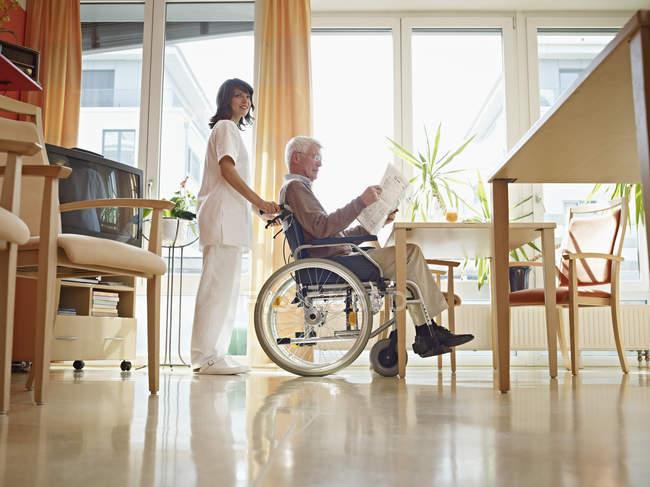 Senior liest Zeitung im Rollstuhl — Stockfoto