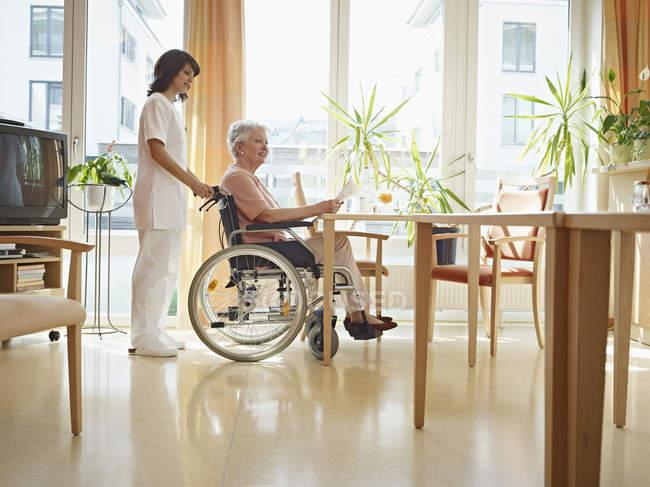 Seniorinnen lesen Zeitung im Rollstuhl — Stockfoto