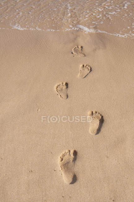 Portugal, Lagos, Footprints on sand against water — Stock Photo