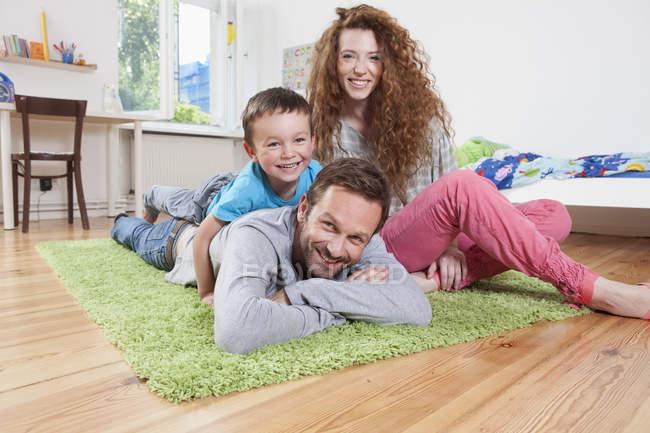 Famiglia rilassante piano sorridente ed esaminante macchina fotografica — Foto stock