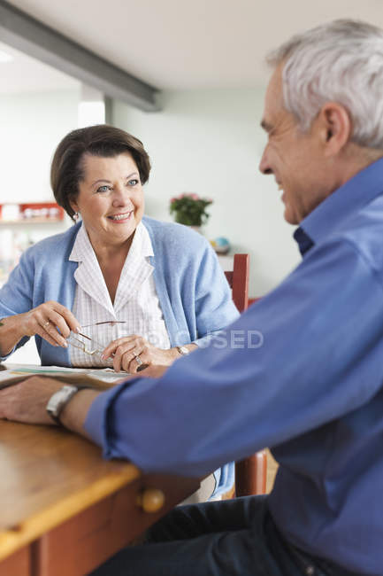Senior man and woman with newspaper, smiling — Stock Photo