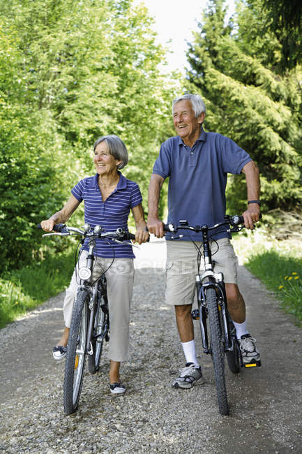 Senior couple with bicycles, smiling — Stock Photo