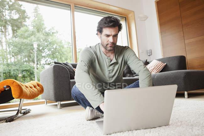 Älterer Mann benutzt Laptop im Wohnzimmer — Stockfoto