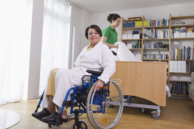 Senior woman sitting on wheelchair another woman arranging medical bed — Stock Photo