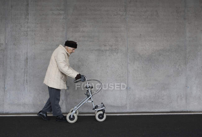 Senior woman walking with wheeled walker — Stock Photo