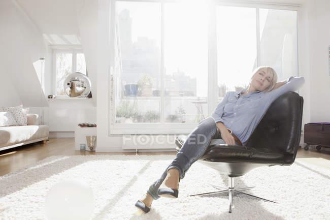 Mulher, relaxante na cadeira na sala de estar — Fotografia de Stock