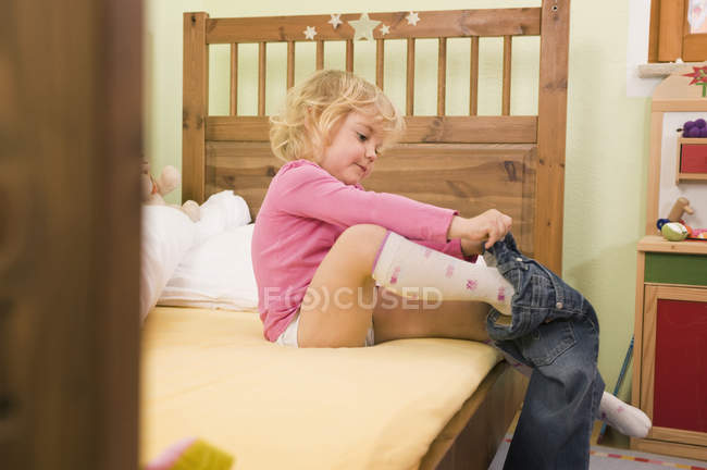 Girl getting dressed on bed — Stock Photo