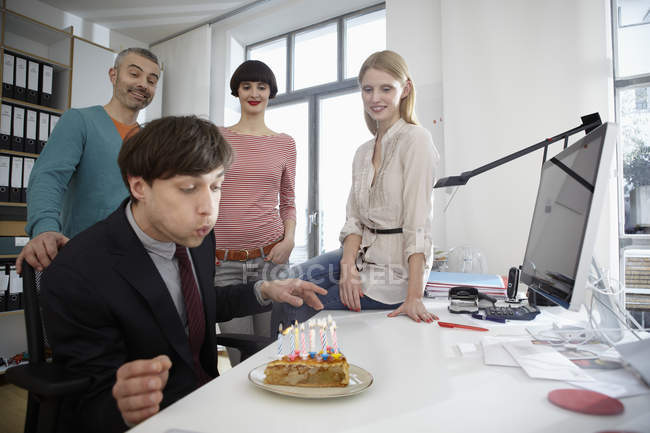 Men and women celebrating birthday in modern office — Stock Photo