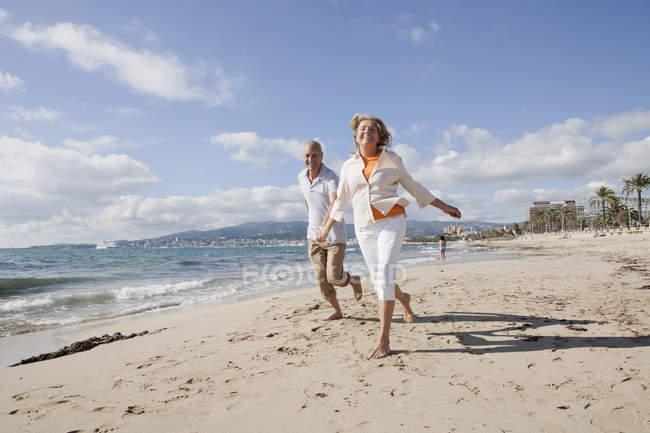 Coppia anziana che corre lungo la spiaggia, sorridente — Foto stock